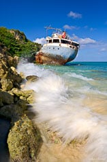 Waves crash around the rusting hulk of a grounded ship at Road Bay in Anguilla, BWI.