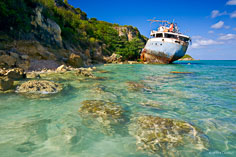 The rusting hulk of a grounded ship sits along the shore at Road Bay in Anguilla, BWI.