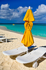 Beach chairs and an umbrella await beach goers at Shoal Bay in Anguilla, BWI.