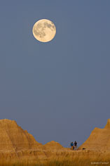 Photographers check their images as the full moon looms above them at Badlands National Park in South Dakota.