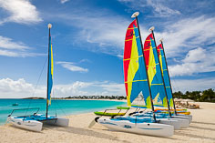 Brightly colored catamarans lined up on the beach at Cap Juluca in Anguilla, BWI.