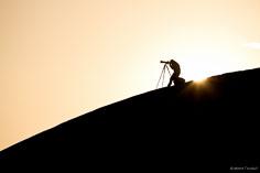 A photographer lines up his shot as the sun rises behind him on the Mesquite Dunes in Death Valley National Park, California.