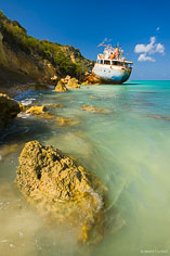 A ship grounded by a past hurricane rests on the rocky shoreline of Road Bay in Anguilla, BWI.
