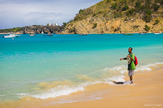 A fisherman brings in his fish net from the waters at Crocus Bay in Anguilla, BWI.