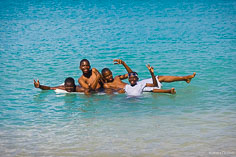 A group of boys having fun playing in the waters of Crocus Bay in Anguilla, BWI.