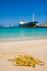 A rope lays coiled on the beach with a cargo ship in the background at Road Bay in Anguilla, BWI.