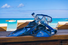 Snorkel gear sits on a beach side table with the waters of Crocus Bay inviting in the background in Anguilla, BWI.