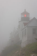 Shortly before sunset, coastal fog surrounds the Bass Harbor Head Light in Acadia National Park in Maine.