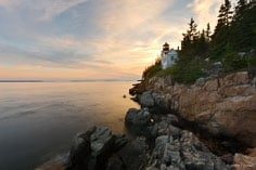 The setting sun turns the clouds pastel colors behind Bass Harbor Head Light in Acadia National Park, Maine.