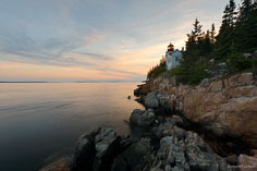 The setting sun turrns the clouds pastel colors behind Bass Harbor Head Light in Acadia National Park, Maine.