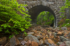 A streambed passes through a portal in the Waterfall Bridge in Acadia National Park, Maine.