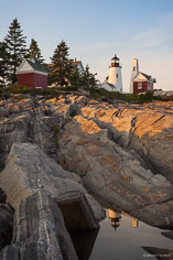 Late day sun reflects the Pemaquid Point Light in a pool on the rocky shore in northeast Maine.