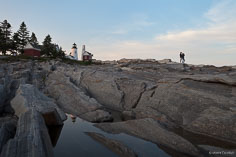 A couple watches the sun set on the rocky shore in front of Pemaquid Point Light in northeast Maine.