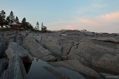 A pool in the rocky shore reflects the Pemaquid Point Light at sunset in northeast Maine.