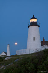 The full moon is seen setting between the bellhouse and Pemaquid Point Light in northeast Maine.