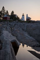 A pool in the rocky shore reflects the Pemaquid Point Light at sunrise in northeast Maine.