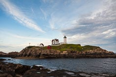 Late day storm clouds add a dramatic touch to the view of Cape Neddick Light on its island in York, Maine.