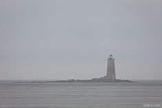 Whaleback Light is surrounded by morning fog far out in the port, as seen from Portsmouth, Maine.