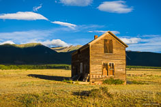 A weathered old house illuminated by early morning light stands out against shadowed mountain peaks outside of Buena Vista, Colorado.