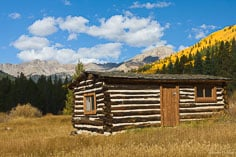 A cabin in the ghost town of Winfield, Colorado with fall color and the Sawatch Mountains in the distance.