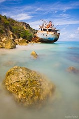 The rusting remains of a grounded ship rests along the shore surrounded by the colorful waters of Road Bay in Anguilla, BWI.